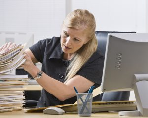 A businesswoman is seated at a desk in an office and is looking through a stack of paperwork.  Horizontally framed shot.